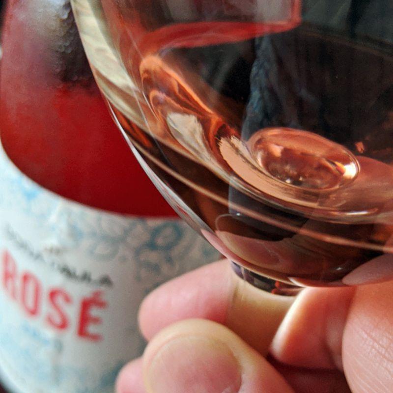 Copa de Doña Paula Rosé 2020 en mano con imagen de botella en el fondo