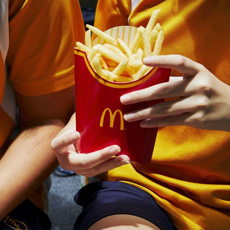 Papas fritas de McDonalds en la mano de una niña